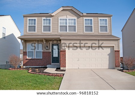 A typical American two story residential home made of brick and vinyl siding in a suburban neighborhood in winter. - stock photo