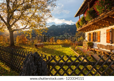 A typical bavarian house with garten. On background a sunset and alp landscape - stock photo