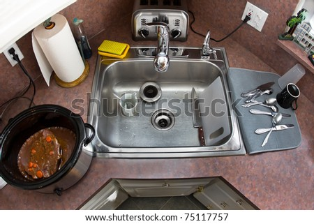 A typical, busy American kitchen from above, showing the sink, toaster, and crock-pot with dinner cooking - stock photo