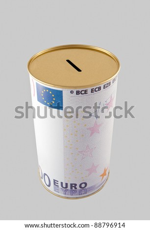 A typical coin bank depicting the symbols of an euro bank note on its cylindrical surface, isolated over a grey background. Includes clipping path. - stock photo