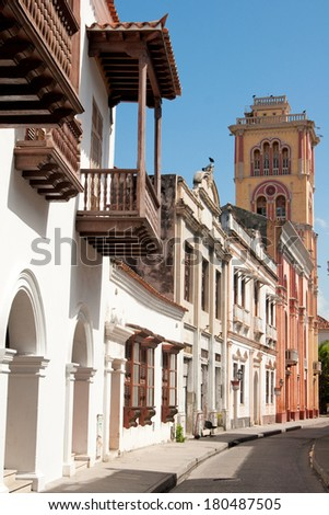 A typical colonial street in Cartagena (Colombia) including the tower of Cartagena Public University (1827), Colombia, South America  - stock photo