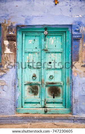 A typical colorful door in a blue house of the center of the blue city of Jodhpur in Rajasthan, India