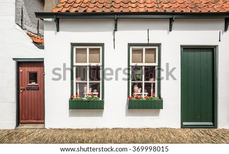 A typical dutch house with a tiled roof, windows painted in white and green, wooden doors and blinds on the windows with a stone pavement along