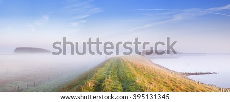 A typical Dutch polder landscape with a dike along a lake. Photographed at the Veerse Meer in the province of Zeeland on a foggy morning. - stock photo