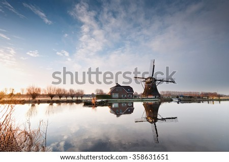 A typical Dutch windmill over tranquil water - stock photo