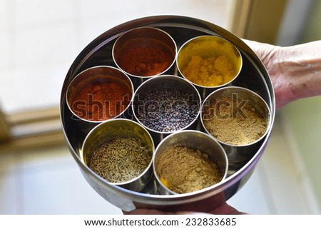 A typical indian spice box with multiple containers. Close up of a hand holding container. - stock photo