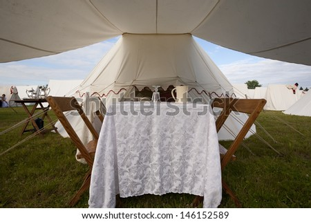 A typical late 1700s or early 1800s dining area set up on soldiers or officers tent awning. - stock photo