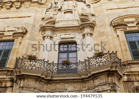 A typical Maltese balcony with a fancy wrought iron railing.