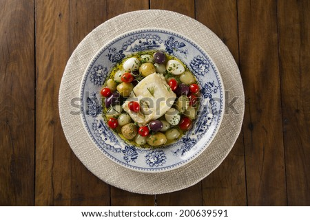 A typical Portuguese dish with codfish called Bacalhau do Porto in a original portuguese plate seen from above - stock photo