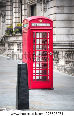 A typical red phone booth in the city of London, capital of the United Kingdom  - stock photo