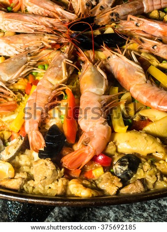 A typical rice dish called Paella with shrimps and shellfish - stock photo