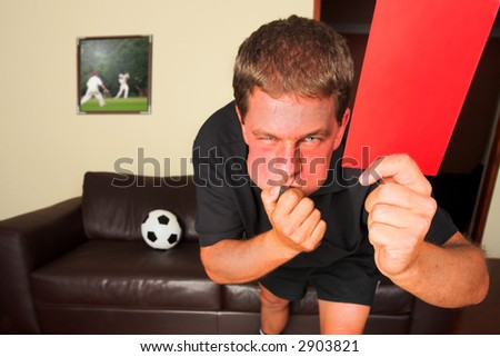A typical sports fan as a referee in his sitting room, blowing a whistle and showing a red card or penalty card to send off an offending player. Cricketers on image in background by same artist. - stock photo