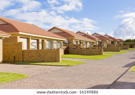 A typical suburban housing development showing a row of similar houses in a compound. - stock photo