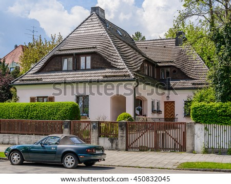 A typical traditional austrian (german) house with a brown tile roof and green hedges and wooden lattice fence building in a residential neighborhood. Retro car parking in front of it. - stock photo