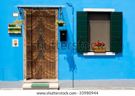 A typical venetian burano house frontage - striking blue wall contrast with bright green window and draped door - stock photo