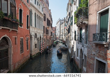 A typical Venetian landscape with river running between buildings and a gondola going through a bridge