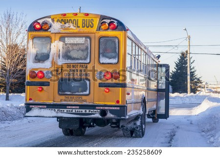 A typical yellow school bus stopped to pick up passengers on an extremely cold winter day. - stock photo