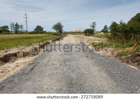A unfinished road construction with sand and gravel layers - stock photo