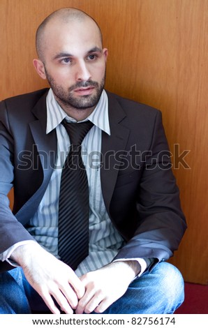 A unhappy man is sitting on the ground - stock photo