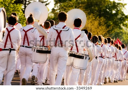 A uniformed band marching beyond the viewer in a parade.