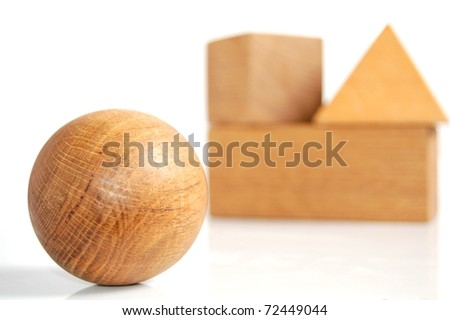 A Unique Set of Wooden Blocks, With a Wooden Sphere in the Foreground and Wooden Blocks Stacked Together in the Background, On White - stock photo