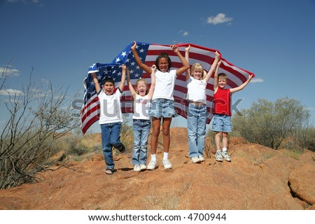 A United Nation:  A diverse group of children enveloped under the American flag outdoors symbolizing our diverse country.
