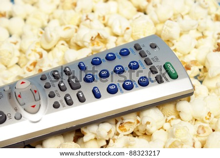 A universal remote on top of some fresh popcorn. - stock photo