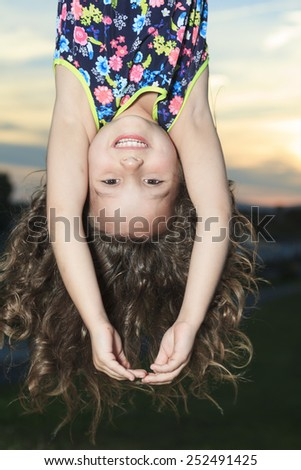 A upside down little girl at the sunset - stock photo
