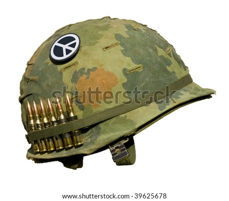 A US military helmet with an M1 Mitchell pattern camouflage cover from the Vietnam war, with six rounds of 7.62mm ammunition and a peace symbol button. - stock photo