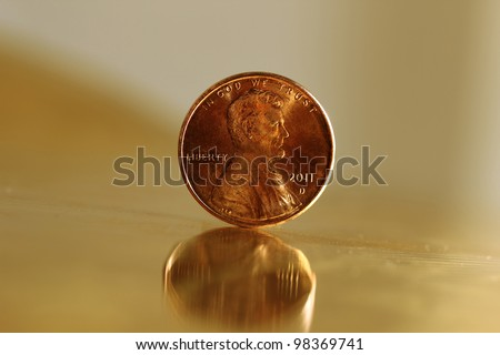 A US penny standing upright on a sheet of golden metal