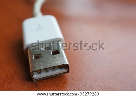 A usb plug on a wooden background
