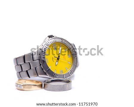 A used and battered mens titanium watch next to titanium and gold wedding rings.