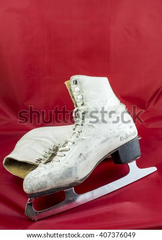 A used pair of women's white figure skates show their age with scuff marks on the toes.  - stock photo