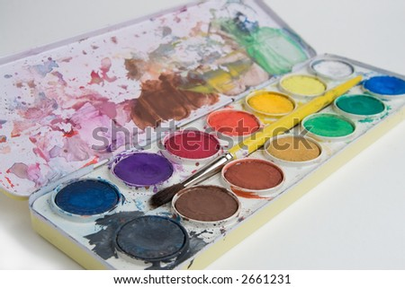A used watercolor paint set with pots of different colored paint and paint brush. - stock photo