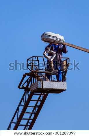 A utility worker changing a street light - stock photo