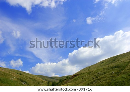 A valley with a blue sky and cumulus clouds. Set in in the Brecon Beacons National Park, Wales, UK - stock photo