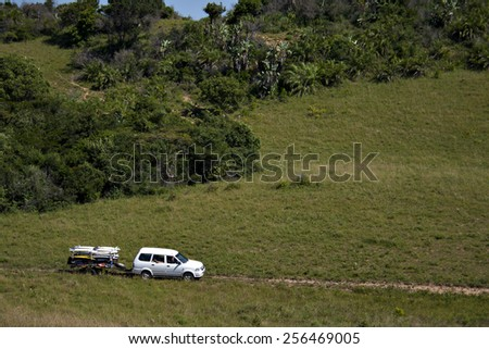 A van tows a trailer full of surfboards as a group of surfers explore a rural landscape in search of waves. - stock photo