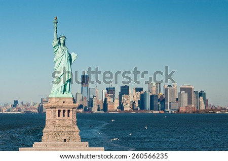 A vantage point in New York Harbor, the iconic island of Manhattan lies just ahead. In the foreground, just ahead and to the left, the Statue of Liberty stands guard. - stock photo