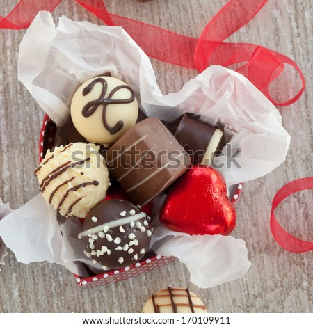 A variety chocolates and truffles on a grey background