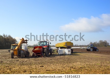 a variety of agricultural equipment gathered to treat and plant seed potatoes in springtime