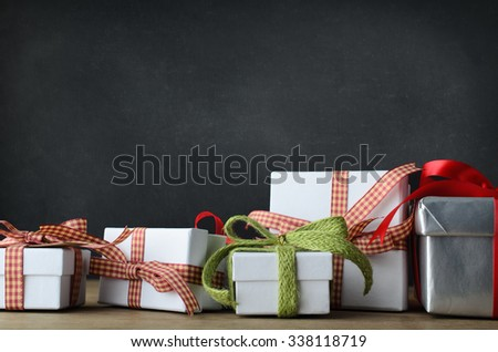 A variety of Christmas gifts in an untidy row extending beyond each side of the frame.  Placed on a desk with blackboard background. - stock photo