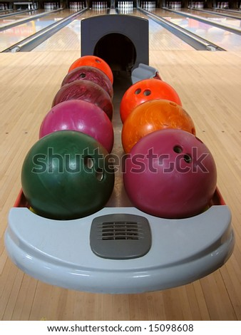 A variety of colorful bowling balls sitting in the ball return at the bowling alley. - stock photo