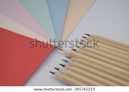 a variety of colors paper and pencils in white isolated background - stock photo