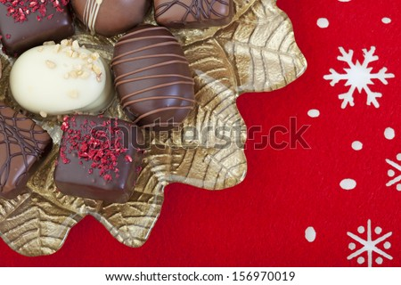 A variety of decadent chocolates arranged on a gold poinsettia plate, on a red felt snowflake mat. - stock photo