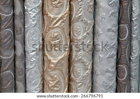 A variety of different bolts of brocade fabric, Colored brocade fabric in a traditional indonesian bazaar - stock photo