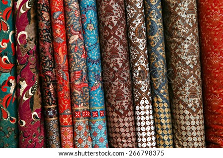 A variety of different bolts of traditional fabric, Colored brocade fabric in a traditional indonesian bazaar - stock photo