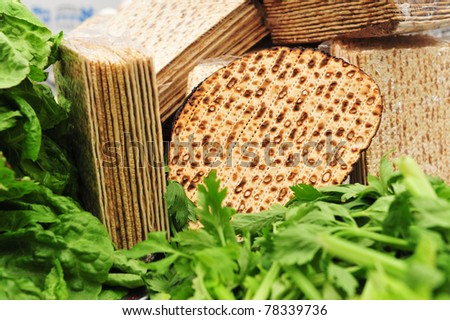 A variety of different types of matza (unleavened bread) surrounded by green vegetables such as lettuce and celery - traditional food used on the Jewish religious holiday feast of Passover (pesach). - stock photo