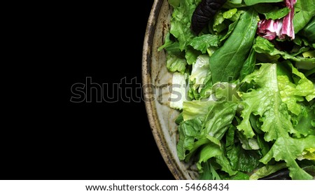 A variety of green lettuce tossed in a salad bowl isolated on a black background - stock photo