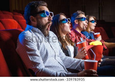 A variety of human emotions of friends holding a cola and popcorn in the cinema.  - stock photo