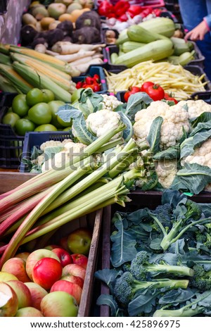 A variety of natural organic fruits and vegetables in the market. People choose outdoor products - stock photo